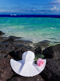 Rose and straw hat lies on stones on the sea background Stock Photography