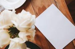 Rose sulla tavola con carta nel retro stile del vaso Fotografia Stock