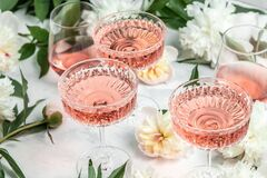 Free Rose Sweet Wine In Glasses With Peony Flowers On White Background, Summer Drink For Party, Wine Shop Or Wine Tasting Concept Stock Photos - 220832443