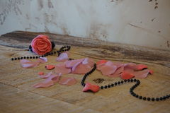 Rose on tabel. Photo of fabric hand made rose, wooden table, beads, pink color Royalty Free Stock Photo