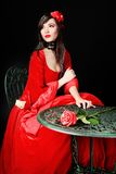 Rose on a table. Portrait of a beautiful woman in medieval era dress. Shot in a studio Stock Photography