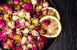 Rose tea buds on dark plate. Rose tea buds and lemon slices on dark plate Royalty Free Stock Images