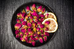 Rose tea buds on dark plate. Rose tea buds and lemon slices on dark plate Royalty Free Stock Photo