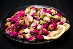 Rose tea buds on dark plate. Rose tea buds and lemon slices on dark plate Royalty Free Stock Image