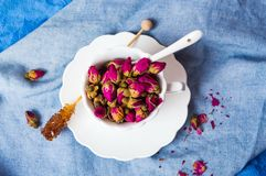 Rose tea buds in a tea cup Stock Images
