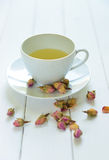 Rose tea cup. Rose flavoured tea in a white cup with dry rose buds scattered around Royalty Free Stock Photography