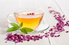 Rose tea and dried petals on wooden table Stock Image