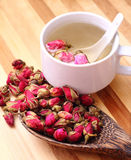 Rose tea. Dried roses, wooden scoop and a cup of rose tea on simple background royalty free stock image