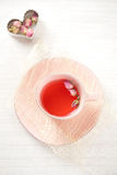 Rose tea in pink cup on white table Stock Photo