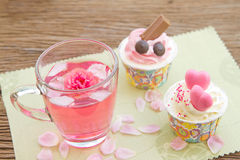 Rose tea  and sweet cupcake on table in the garden Royalty Free Stock Images
