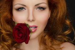 Rose in the teeth of woman with beautiful hair Stock Photography