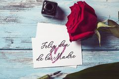 Rose and text happy mothers day in spanish. A red rose, an ink bottle, a nib pen and a piece of paper with the text feliz dia de la madre, happy mothers day royalty free stock images