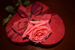 Rose on top of heart shaped red box. Close up of pink rose on top of heart shaped red box with red bow Royalty Free Stock Photography
