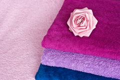 Folded towels. A background of colored folded towels and a pink paper rose Royalty Free Stock Image