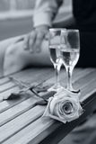 Rose and two wineglasses in black and white. Rose and two wineglasses with champagne on the bench in black and white with soft blue tint Stock Image