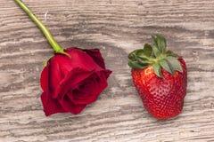 Rose und Erdbeere auf Holz lizenzfreie stockfotografie