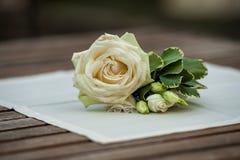 Rose und grüne Blätter auf weißer Serviette auf hölzerner Tabelle stockbild