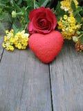 Rose und rotes Herz auf altem hölzernem Hintergrund, bunte Blumen Stockfoto