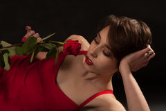 A rose for Valentine's Day. A young woman lies on the ground while holding a  single rose Royalty Free Stock Photography