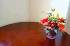 Rose Vase giallo arancione artificiale variopinta sulla Tabella di legno e Immagine Stock