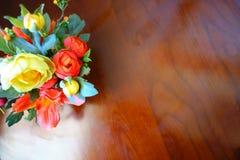 Rose Vase giallo arancione artificiale variopinta sulla Tabella di legno vin Fotografia Stock