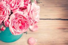 Rose in vaso su fondo di legno Immagine Stock
