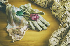 Rose and a veil on a glove. Poetic composition with a rose lying on an elegant glove between a veil and a table cloth in vintage look Royalty Free Stock Photography