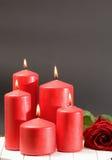 Rose, velas rojas ardiendo en una tabla Fotos de archivo