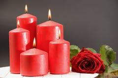 Rose, velas rojas ardiendo en una tabla Imagenes de archivo
