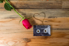 Rose and vintage audio cassette with loose tape shaping one hear Royalty Free Stock Photos