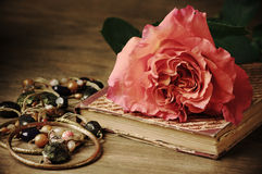 Rose and vintage book. Rose, jewellery and vintage book on wooden table royalty free stock photo