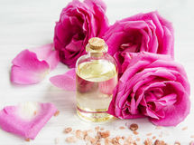 Rose water in a bottle with roses flowers and petals Royalty Free Stock Photos