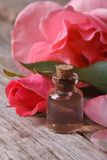 Rose water in a glass bottle on a background of pink roses Royalty Free Stock Images