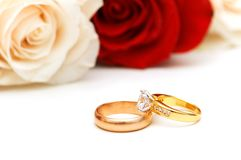 Rose and wedding rings isolated on the white Royalty Free Stock Photo