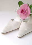 Rose and Wedding slippers. Beautiful highkey satin white wedding shoes and single pretty pink rose Stock Images