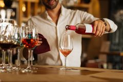 Rose wine being poured in the glass. Premium drink. Rose wine being poured in the glass by a nice smart handsome barman Stock Photos