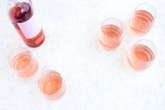 Rose Wine Bottle e vetri riempiti su bianco Immagini Stock