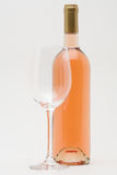 Rose wine bottle with empty glass. In front stock images