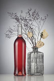 Rose wine bottle with no label. Next to withered white roses in a vase Stock Photos