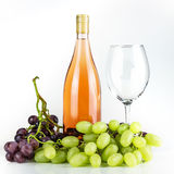 Rose wine bottle, wineglass and grapes. Stock Photos
