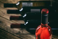 Rose wine bottle on wooden background stock photo