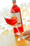 Rose Wine Bottle y vidrio lleno en una mano Imagen de archivo libre de regalías