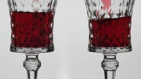 Rose Wine De rode wijn giet in twee wijnglazen over witte achtergrond stock video