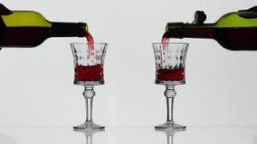 Rose Wine De rode wijn giet in twee wijnglazen over witte achtergrond stock footage
