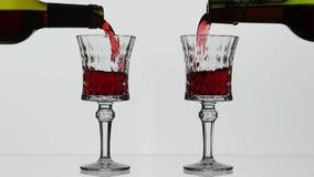 Rose Wine De rode wijn giet in twee wijnglazen over witte achtergrond stock videobeelden