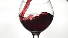 Rose Wine De rode wijn giet in wijnglas over witte achtergrond Langzame Motie stock video