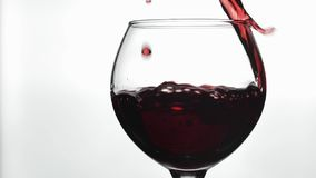 Rose Wine De rode wijn giet in wijnglas over witte achtergrond Langzame Motie stock footage
