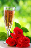 Rose wine in glass and roses Royalty Free Stock Photography