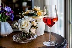Rose Wine met bloemen natuurlijk licht stock afbeelding