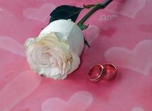 Rose y anillos de bodas en un fondo con los corazones Fotos de archivo